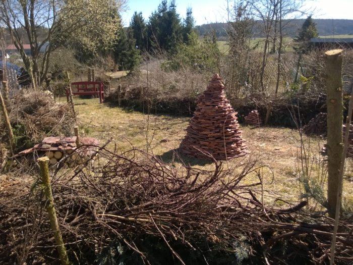 Dachziegelpyramide inmitten von Totholz
