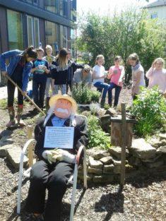 Albert Einstein und die Kinder der Garten AG. Im Schulgarten entsteht eine Kräuterschnecke mit b ...