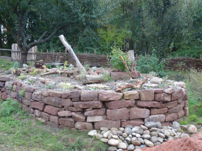 Die Trockenmauer und auch das Totholz oben können Nisthilfen bzw. Lebensraum für Wildbienen sein!