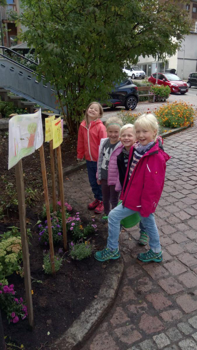 Das Gartengrundstück und die gemalten Bilder werden betrachtet. Die Kinder sind sehr stolz auf i ...