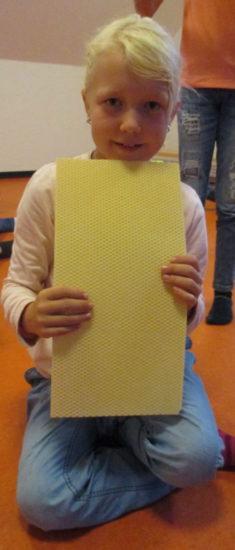 Emma zeigt eine Bienenwachsplatte